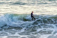 Surfer at Manhattan Beach, California. Surfing the waves in a wetsuit Stock Image