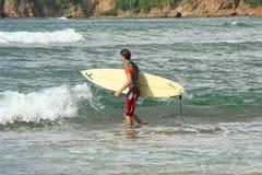 Surfer marchant avec sa planche de surf sur une plage Photos stock