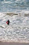 Surfer marchant dans l'eau dans la mer avec la planche de surfing Images stock