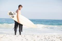 Surfer marchant sur la plage avec une planche de surf Photos stock