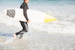 Surfer marchant sur la plage avec une planche de surf Photo stock