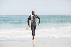Surfer marchant vers la mer avec une planche de surf Image stock