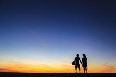 Surfer meets photographer : lovers. Sunset surfer kalalau kauai hawaii  surfboard sunrise love canon film photographer water sky beach sand lovers holding hands Stock Images