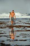 Surfer mit Surfbrett auf einer Küstenlinie von Sumbawa, Indonesien Stockbilder