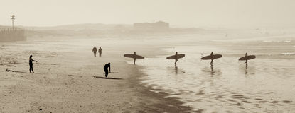 Surfer Morning. Surfers head out with surfboards at Muizenberg Beach near Cape Town Stock Photography