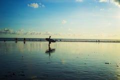 Surfer naar huis achter bij Kuta-Strand, Bali-Indonesië in de zonsondergangtijd stock afbeelding