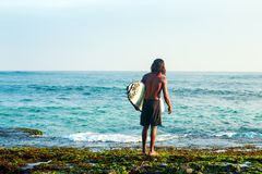 Surfer near the sea. The surfer is holding a surfboard on the Indian Ocean shore Stock Photography