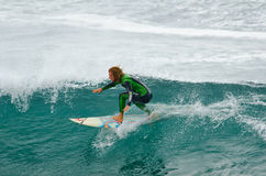 Surfer near the top of a wave Stock Images
