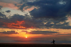 Surfer on the ocean beach at sunset or sunrise. Surfer on the ocean beach at sunset with dark clouds Stock Image