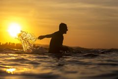 Surfer in ocean at sunset time. Surfer waiting in the line up for a wave at sunrise or sunset Stock Image