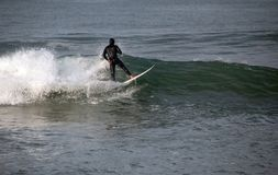 Surfer op golf bij sandbar waar Santa Clara River in de Vreedzame Oceaan bij Ventura California-U leegmaakt stock fotografie