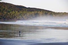 Surfer op nevelige Cox-Baai, Tofino, Brits Colombia, Canada Stock Foto's