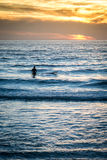 Surfer op strandzonsondergang op strand en golven Stock Afbeeldingen