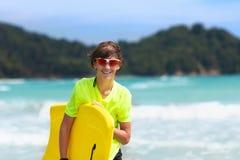 Surfer op tropisch strand Jongen het surfen royalty-vrije stock afbeelding