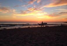 Surfer op zonsondergangstrand Stock Afbeeldingen
