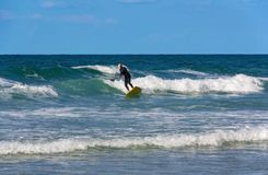 A surfer over the age of 60 slides on the waves. A sea of color turquoise and sky blue. On sea waves of. In the sea, an elderly man, in good physical shape, who stock images