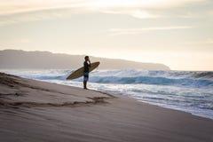Surfer looking at breaking waves on North Shore at Hawaii Stock Photo