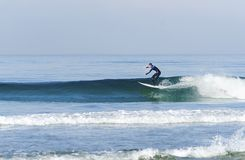 Surfer, Pacific beach, San Diego, California. An American professional surfer man wearing a wet suit in the Pacific beach in San Diego, Southern California, in Stock Photography