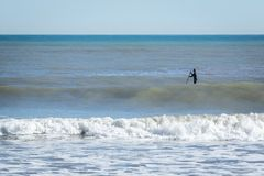 Surfer with paddle board catching the wave.  royalty free stock photos