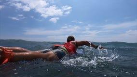 Surfer paddles in the ocean