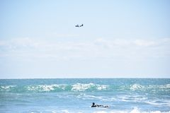 Surfer Paddles Out as Airplane Flies Over Horizon. A surfer wearing a wetsuit is paddling out towards the break as an airplane flies over the blue horizon not Royalty Free Stock Images
