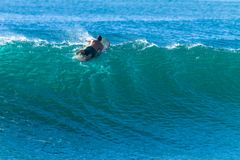 Free Surfer Paddles Over Cresting Wave Escape Beating Stock Photo - 141850810
