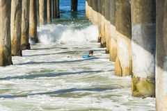 Surfer paddless between pier piles California Stock Photography