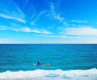 Surfer paddling on a surfboard. In the summertime Stock Image