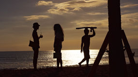 Surfer passes two women on beach. Silhouette of a surfer passing two women in talking Stock Images