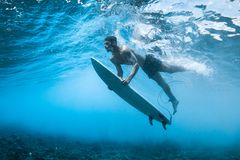 Surfer performs dive. The duck dive with his surfboard under the wave royalty free stock photo
