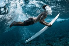 Surfer performs dive. The duck dive with his surfboard under the wave and exhales air into the water royalty free stock photo