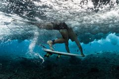 Surfer performs dive. With his surfboard Duck Dive under the powerful wave at shallow reef area stock photos