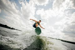 Surfer performs his professional abilities and skills. Athletic healthy surfer performs his professional abilities and skills, rides the waves in a summer river Royalty Free Stock Images