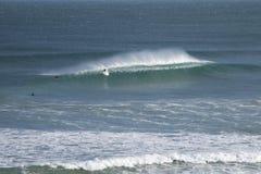 Surfer prenant une crête de balise Images stock