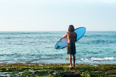Surfer preparing to dive into the water. The surfer is holding a surfboard on the Indian Ocean shore Stock Photography