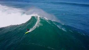 Surfer professionnel glissant dans les vagues mousseuses blanches énormes éclaboussant dans l'eau bleue profonde d'océan de turqu banque de vidéos