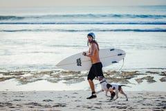 Surfer pulsant avec son chien Image stock
