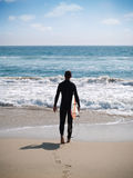 Surfer ready to surf. Surfer in black wet suit about to start a session Stock Images
