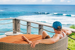 Surfer relaxing in lounge on roof veranda with sea view. Young surfer relaxing in lounge on roof veranda with beautiful tropical sea view. Positive man look at royalty free stock photo