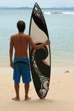 Surfer restant sur la plage avec la planche de surfing géniale d'arty photographie stock