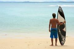 Surfer restant sur la plage avec la planche de surfing géniale d'arty photographie stock libre de droits