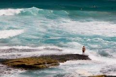 Surfer restant sur une roche Photo stock