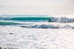 Surfer on blue barrel wave. Winter surfing in ocean Stock Photography