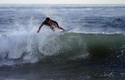 Surfer Rides the Crest. An unknown surfer rides the crest of a wave, along the Pacific Coast, near Malibu Stock Photos