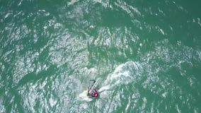 Surfer rides gleaming azure ocean waves stock footage