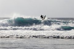 Surfer rides on a wave on bali - Asia stock photos