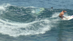 A surfer rides a wave in the surf at the ocean blue in the surf spot. stock footage