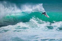 Surfer riding big wave. At critical angle at Padang Padang beach in Bali Stock Photo