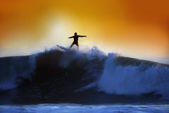 A surfer riding a big wave at sunset. In an orange sky Royalty Free Stock Photos
