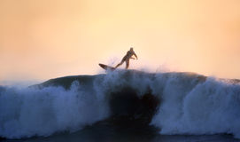 A surfer riding a big wave at sunset Stock Photos